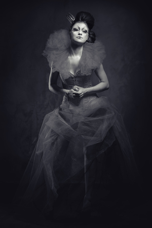 jabot: Queen. Woman with creative makeup in fluffy dress posing indoors. Black and white