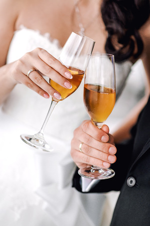 tomando vino: Manos de la novia y el novio con copas de champán Foto de archivo