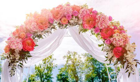 Schöne weiße Hochzeitsbogen mit rosa und roten Blumen im Freien dekoriert Standard-Bild - 43471081