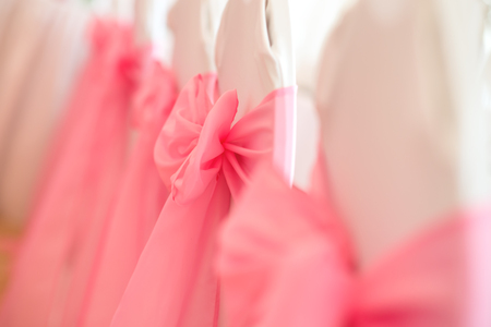 wedding chairs: Close-up of white wedding chairs with pink ribbon. Selective focus Stock Photo