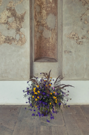 yellow wildflowers: Bouquet of wildflowers on a wooden floor against weathered wall