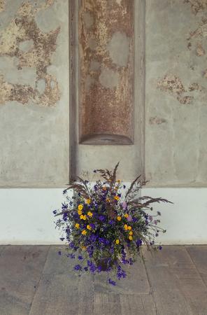 fiori di campo: Mazzo di fiori di campo su un pavimento di legno contro la parete intemperie