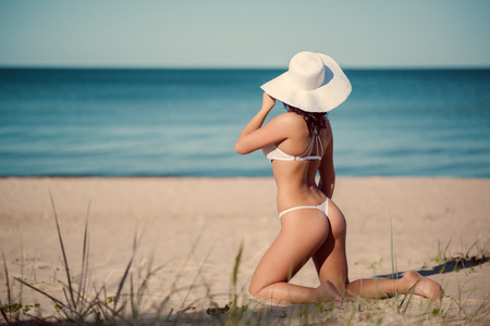 gstring: Sexy woman in white lingerie and white hat posing on the beach near the sea Stock Photo