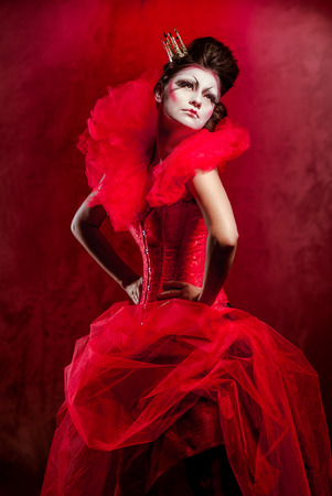 evening dress: Red Queen. Woman with creative make-up in fluffy red dress posing indoors