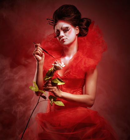 jabot: Red Queen. Woman with creative make-up in fluffy red dress with a white rose and paintbrush posing indoors
