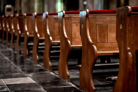 Houten kerkbanken in een rij in een kerk Redactioneel