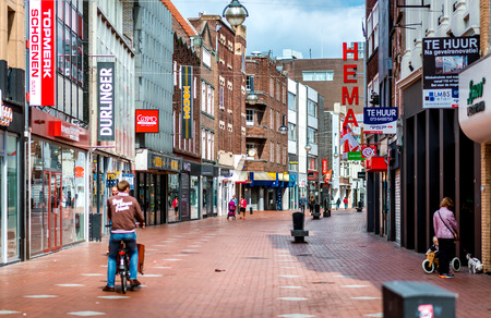 retail store: Eindhoven, Netherlands - May 24, 2015: People walking in the Eindhoven main commercial street. It is one of the most famous shopping street in the city, a narrow but long street with plenty of stores, bars and clubs