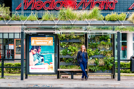 wait: Eindhoven, Netherlands- May 24, 2015: Girl at a Eindhoven green bus stop. The green bus stop was created as part of a competition organized by the Municipality of Eindhoven back in 2009. The bus station was featured during 2009 Dutch Design Week