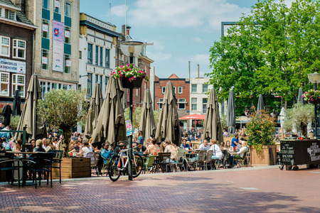 eindhoven: Eindhoven, Netherlands - May 24, 2015: People sitting at outdoors restaurant in the main square of Eindhoven in sunny spring day. It is popular touristic place, with plenty of restaurants, bars, stores and clubs Editorial