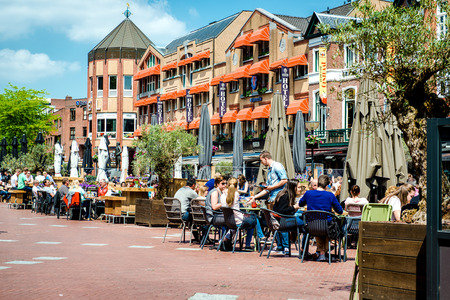 main street: Eindhoven, Netherlands - May 24, 2015: People sitting at outdoors restaurant in the main square of Eindhoven in sunny spring day. It is popular touristic place, with plenty of restaurants, bars, stores and clubs Editorial