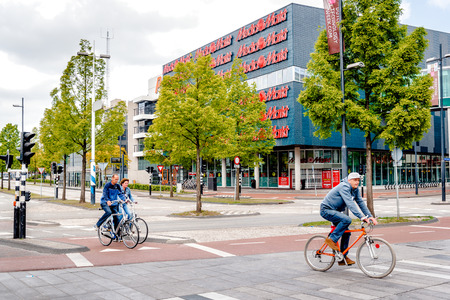 eindhoven: Eindhoven, Netherlands- May 24, 2015: People crossing the street by bicycle. Bicycles are popular way to get around for the Dutch. Eindhoven is one of the five nominees to become best Cycling City of the Netherlands in 2014
