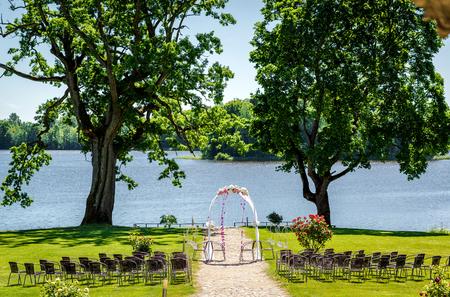 結婚式: 湖畔の結婚式。結婚式の椅子と芝生の上の結婚式のアーチ 写真素材