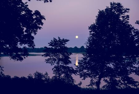 lake sunset: Night landscape of moon and lake. Pink, violet and black colors Stock Photo