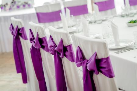 morado: Primer plano de las sillas blancas de la boda con la cinta p�rpura Foto de archivo