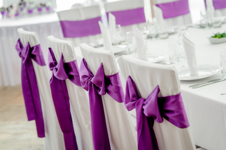 morado: Primer plano de las sillas blancas de la boda con la cinta púrpura Foto de archivo