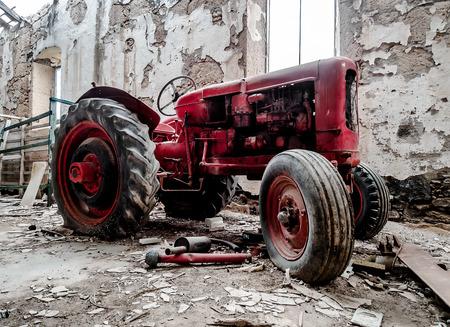 rusty car: Old, broken tractor indoors