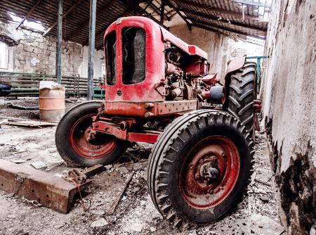 old tractors: Old, broken tractor indoors