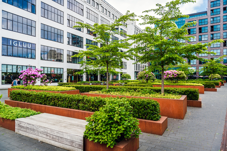 commercial district: Eindhoven, Netherlands- May 24, 2015: Eindhoven downtown. Lush bushes and benches in the office complex park