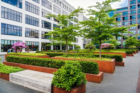 anuncio publicitario: Eindhoven, Países Bajos-24 de de mayo de, 2015: el centro de Eindhoven. arbustos frondosos y bancos en el parque complejo de oficinas Editorial