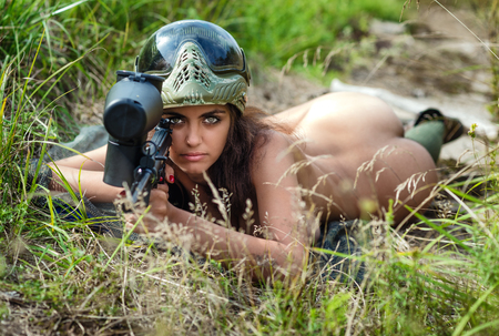 nude sport: Young naked brunette with paintball gun lying outdoors Stock Photo
