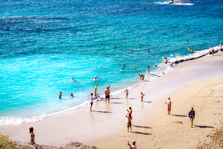 adeje: Tenerife, Canary Islands- January 1, 2015: People in the picturesque El Duque beach, Tenerife. Canary islands, Spain
