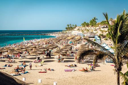 adeje: Tenerife, Canary Islands- January 1, 2015: People sunbathing in the picturesque El Duque beach, Tenerife. Canary islands, Spain
