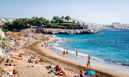 canarian: Tenerife, Canary Islands- January 5, 2015: People swimming and sunbathing on the picturesque El Duque beach, Tenerife. Canary islands, Spain Editorial