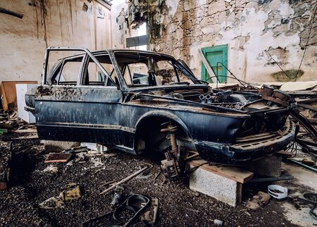 ruinous: Old wrecked car inside of ruinous building