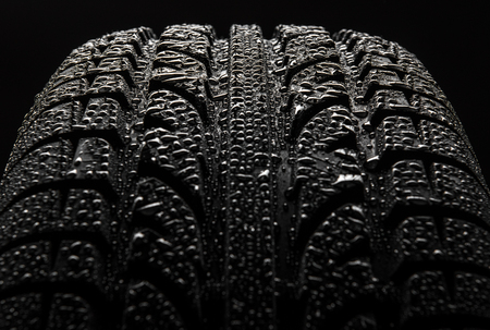 Tire with water drops over black background