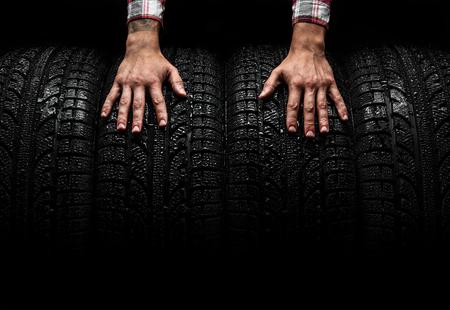 llantas: Hombre en las manos en un neumáticos de coche, tiro del estudio