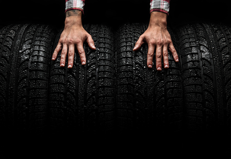 Men's hands on a car tires, studio shot Stock Photo