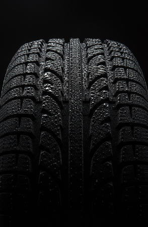 black grip: Tire with water drops over black background