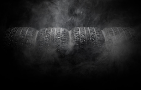 smoke background: Close-up of car tires with smoke over black background