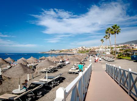 adeje: Tenerife, Canary Islands- December 20, 2014: People walking along the seafront promenade. Fanabe beach. Costa Adeje. Tenerife. Canary Islands. Spain