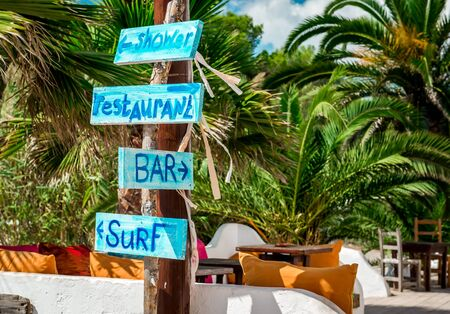 nudist: Signboard with arrows. Shower, bar, restaurant and surf directions on the Ibiza nudist beach. Balearic islands, Spain Stock Photo