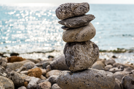large: Art of stone balance, piles of stones on the beach. Ibiza, Spain Stock Photo