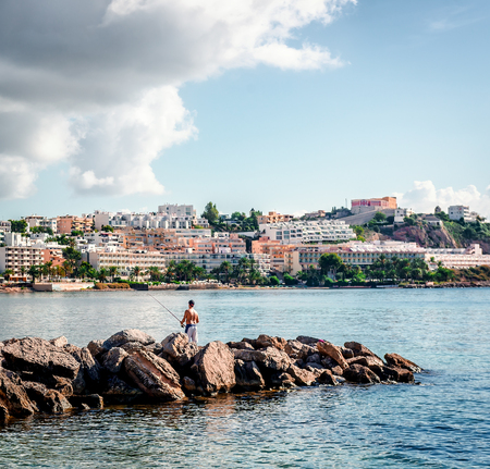 townscape: Ibiza, Spain- September 20, 2013: Man with fishing rod against Ibiza townscape. Balearic islands. Spain Editorial