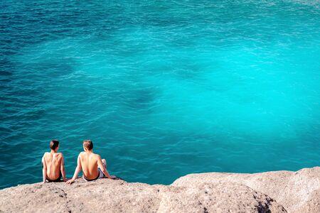 adeje: Two unrecognizable guys on a rock in El Duque beach. Costa Adeje. Tenerife. Canary islands, Spain. Summer vacations concept