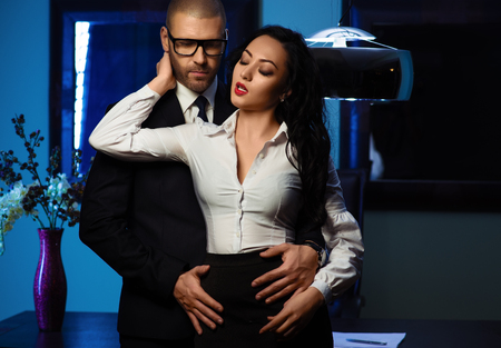 seduction: Couple indoors. Sensual brunette and handsome businessman. Office romance concept Stock Photo