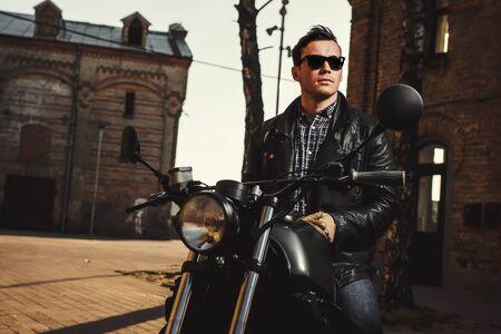 유행: 남자는 야외 카페 레이서 오토바이에 앉아