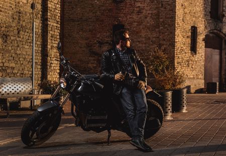 optimized: Man with a cafe-racer motorcycle outdoors