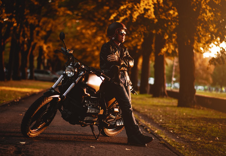 Motorcyclist with a cafe-racer motorcycle outdoors Standard-Bild