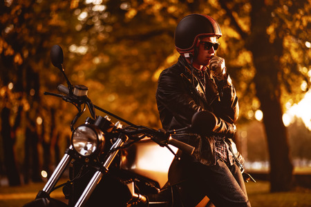 Motorcyclist with a cafe-racer motorcycle outdoors Zdjęcie Seryjne
