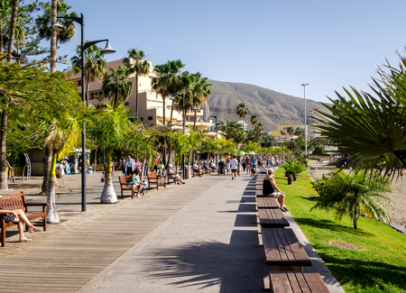 waterfront: Tenerife, Spain-December 22, 2014: People walking along the Los Cristianos promenade.  Los Cristianos is one of the most popular and well-known resorts in the Tenerife
