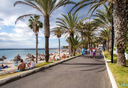 americas: Tenerife, Spain-January 09, 2015: People walking along the Las Americas seafront promenade. Las Americas is one of the most popular and well-known resorts in Tenerife