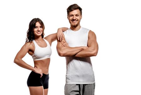 fitness: Mujer atlética joven y hermosa y el hombre aislado en el fondo blanco