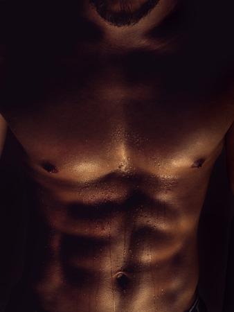desnudo masculino: Individuo atlético. Primer plano de un abdominales perfectos con gotas de agua