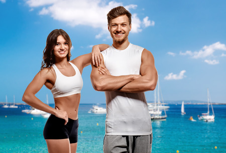 healthy looking: Young and beautiful athletic woman and man over turquoise bay background