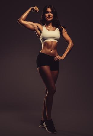woman muscle: Beautiful young athletic woman showing biceps, studio shot Stock Photo