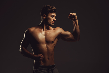 nude stomach: Athletic handsome man showing biceps muscles, studio shot